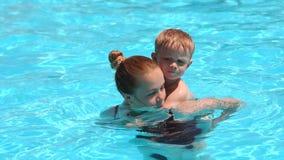 Una familia alegre, madre joven con su hijo, tiene la diversión y juego en la piscina
