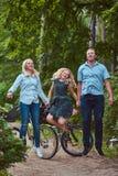 Una familia atractiva se vistió en ropa casual en un paseo de la bicicleta, tiene la diversión y salto en un parque Imagenes de archivo
