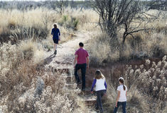 Una familia camina en Murray Springs Clovis Site Imagenes de archivo