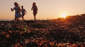Una familia con sacudidas de un niño a lo largo de la línea de la resaca al mar en la puesta del sol almacen de video