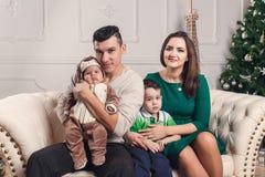 Una familia de cuatro miembros feliz joven en interior del Año Nuevo Fotos de archivo