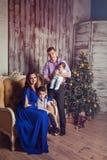 Una familia de cuatro miembros joven en interior del Año Nuevo Fotos de archivo