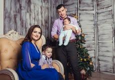 Una familia de cuatro miembros joven en interior del Año Nuevo Fotografía de archivo libre de regalías