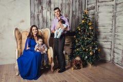Una familia de cuatro miembros joven en interior del Año Nuevo Fotos de archivo libres de regalías