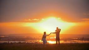 Una familia de 3 entra la puesta del sol almacen de metraje de vídeo