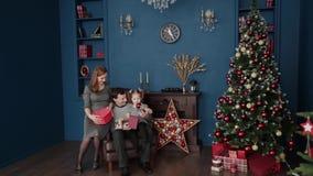 Una familia de tres abre los regalos cerca de la chimenea, la Navidad 2019 del Año Nuevo almacen de metraje de vídeo