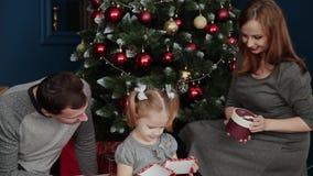 Una familia de tres abre los regalos cerca de la chimenea, la Navidad 2019 del Año Nuevo metrajes