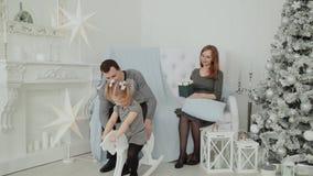 Una familia de tres que se sientan en el sofá y que hablan en Nochevieja, la Navidad 2019 almacen de metraje de vídeo