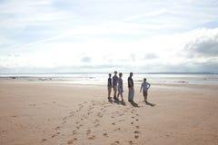Una familia en la playa en el sol Foto de archivo libre de regalías