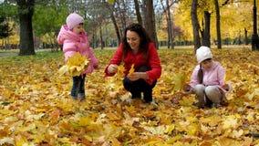 Una familia en un parque del otoño recoge las hojas La mamá y dos hijas juegan con las hojas en el parque en la caída Hermoso almacen de video