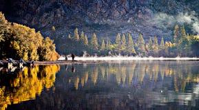 Una familia está lista para montar un barco en un lago inmóvil en la sierra del este área en un verano el domingo por la mañana fotografía de archivo