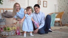 Una familia est? sonriendo en cama, donde est?n el padre y la madre despu?s de su hija, la hija intenta bailar almacen de metraje de vídeo
