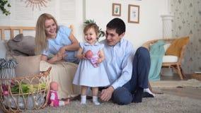 Una familia est? sonriendo en cama, donde est?n el padre y la madre despu?s de su hija, la hija est? sosteniendo una mu?eca almacen de video
