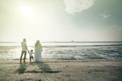Una familia está teniendo vista agradable de la puesta del sol en la playa concepto de la vinculación de la relación de familia fotos de archivo libres de regalías