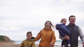 Una familia feliz con los niños en ropa caliente da un paseo por el mar en un día ventoso almacen de metraje de vídeo