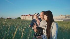 Una familia feliz de tres personas camina a lo largo del campo de trigo entre las espiguillas verdes En la distancia, edificios d metrajes