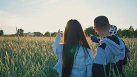 Una familia feliz de tres personas camina los campos de trigo entre las espiguillas verdes en los rayos del sol poniente Feliz metrajes