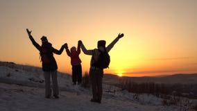 Una familia feliz, de tres personas, se coloca en una montaña en invierno almacen de metraje de vídeo