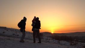 Una familia feliz, de tres personas, se coloca en una montaña en invierno almacen de video