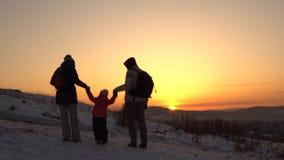 Una familia feliz, de tres personas, se coloca en una montaña en invierno metrajes