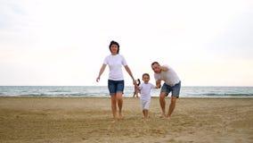 Una familia feliz de tres que camina a lo largo de la playa arenosa del mar, mirando hacia el cielo, mostrando con una mano, en l almacen de video