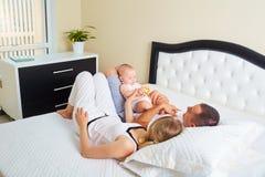 Una familia feliz El padre, la madre y el hijo tienen un juego de la relajación en thei fotos de archivo