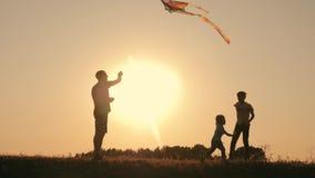 Una familia feliz Familia en el verano en el lanzamiento de la puesta del sol una cometa en el cielo metrajes