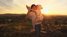 Una familia feliz en puesta del sol, madre está deteniendo a su hija en sus brazos almacen de metraje de vídeo