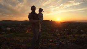 Una familia feliz en puesta del sol, padre está deteniendo a su hija en sus brazos almacen de video