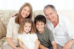 Una familia feliz en su sofá que mira la cámara Imagen de archivo libre de regalías