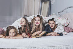 Una familia feliz grande La mamá lee un libro a sus niños en cama foto de archivo libre de regalías