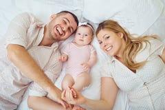 Una familia feliz juega con un niño en una cama adentro dentro foto de archivo libre de regalías