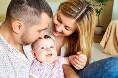 Una familia feliz Mamá y papá con el bebé en el cuarto Imágenes de archivo libres de regalías