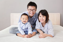 Una familia feliz que se sienta en la cama blanca Fotografía de archivo