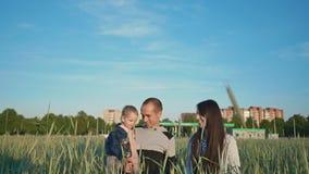 Una familia feliz va con placer sobre el campo de trigo entre las espiguillas verdes En la distancia, edificios de la ciudad almacen de video