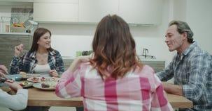 Una familia grande carismática tiene un rato del almuerzo junta que come la comida sana y que pasa el tiempo que sorprende junto almacen de metraje de vídeo
