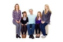 Una familia grande ordinaria que se sienta en el sofá Imagen de archivo libre de regalías