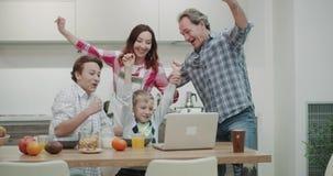 Una familia hermosa por la mañana mientras que tomaba el desayuno que miraba un partido junta del ordenador portátil y feliz puso almacen de video