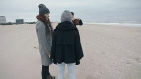 Una familia joven agradable con un perro está riendo para un paseo a lo largo de la playa metrajes