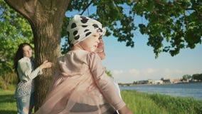 Una familia joven así como una pequeña hija en un parque debajo de un árbol cerca de un lago El padre mantiene a la hija sus braz almacen de metraje de vídeo