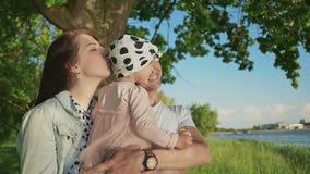 Una familia joven así como una pequeña hija en un parque debajo de un árbol por el lago El padre detiene a la hija en el suyo almacen de metraje de vídeo