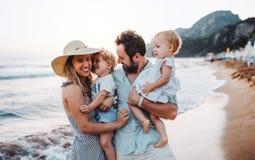 Una familia joven con dos ni?os del ni?o que se colocan en la playa el vacaciones de verano fotografía de archivo libre de regalías
