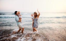 Una familia joven con dos ni?os del ni?o que se divierten en la playa el vacaciones de verano foto de archivo libre de regalías