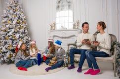 Una familia joven con los niños se está preparando para celebrar Christma Imagen de archivo