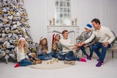 Una familia joven con los niños se está preparando para celebrar la Navidad Foto de archivo libre de regalías
