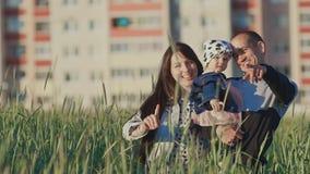 Una familia joven con una pequeña hija en sus brazos en un campo del trigo entre las espiguillas verdes En el fondo del almacen de video