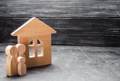 Una familia joven con un niño se está colocando cerca de la casa Casa y figuras de madera de la gente El concepto de búsqueda de  Foto de archivo libre de regalías