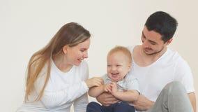 Una familia joven feliz que pasa tiempo con un hijo joven en un hogar nuevo almacen de video