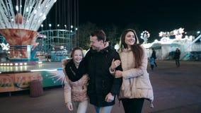 Una familia joven hermosa camina en la noche en el parque de atracciones en medio de atracciones luminosas almacen de video