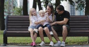 Una familia joven se está sentando en un banco de parque y se está divirtiendo almacen de video